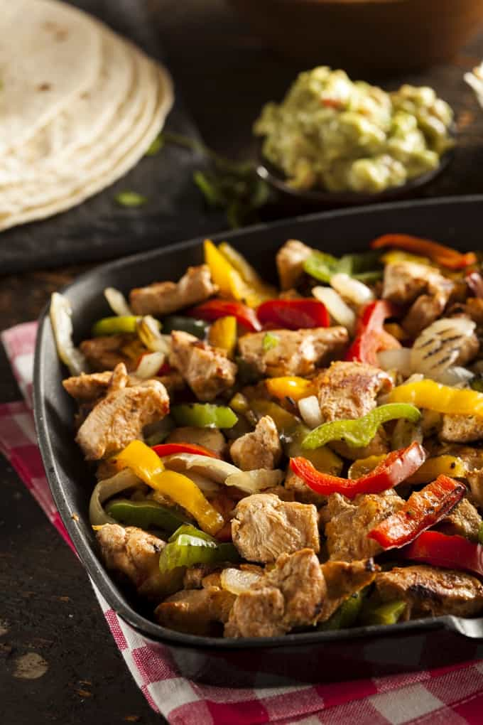 Homemade Chicken Fajitas with Peppers, Onions, Tortillas and Guacamole in the background