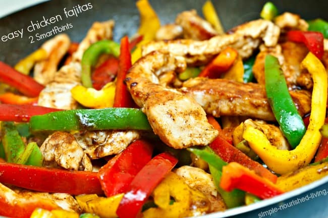 Chicken fajitas with red, green and yellow bell peppers in pan.