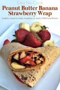 Peanut Butter Banana Strawberry Wrap cut in half on plate with fresh strawberries and banana slices