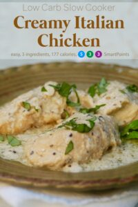 Slow cooker 3-ingredient creamy italian chicken garnished with fresh chopped basil on serving platter.