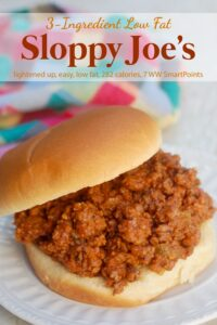 Sloppy Joe on hamburger bun on white plate with colorful napkin in the background.