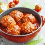 Meatballs with rice and tomato sauce in a red pot