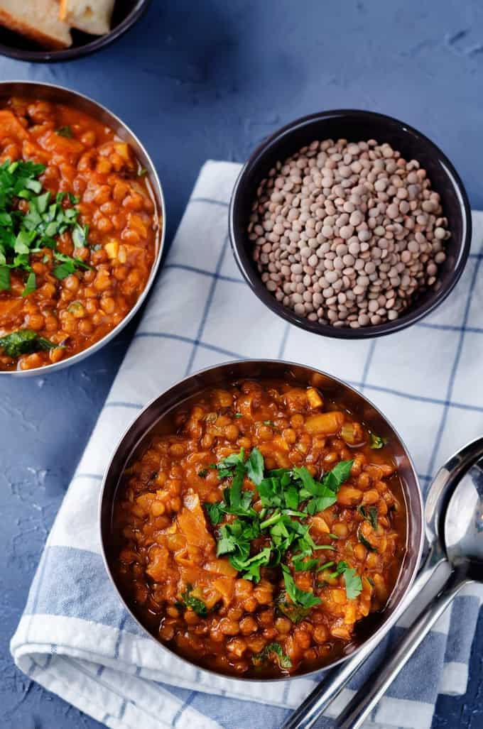 Two bowls of lentil stew with a bowl of dry lentils sitting on a dish towel on a blue table