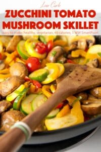 Zucchini, mushrooms and tomatoes in skillet with wooden spatula.