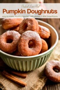 Baked pumpkin donuts sprinkled with powdered sugar in green bowl.