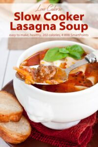 Bowl of lasagna soup topped with cheese and lasagna soup with fresh bread on the side