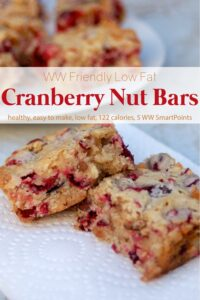 Low-fat cranberry nut bars on white napkin with plate of cranberry bars in background.