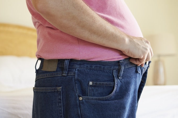 Close up of overweight man wearing pink t-shirt trying to fasten his jeans