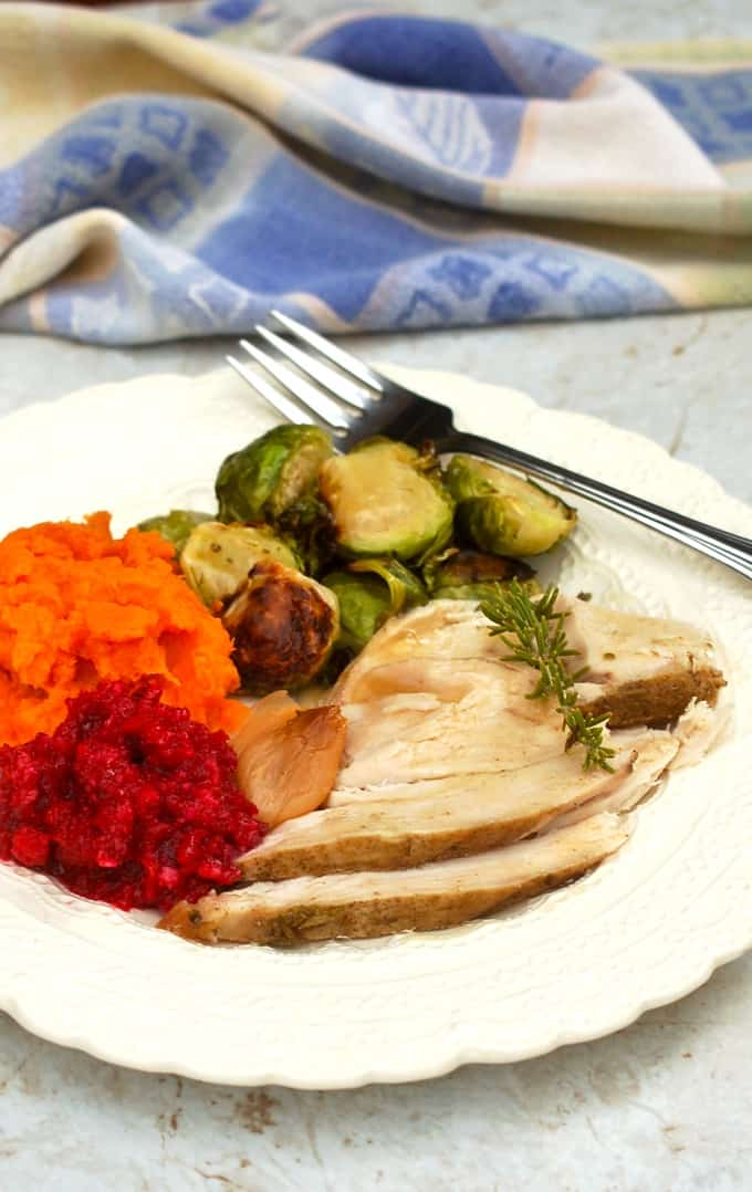 Sliced turkey breast, mashed sweet potatoes, fresh cranberry relish, roasted brussels sprouts on a white plate with a fork.