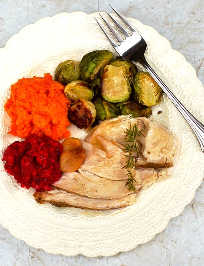 Slow cooker garlic turkey breast with roasted Brussels sprouts, mashed sweet potatoes and cranberry sauce on white dinner plate with fork.