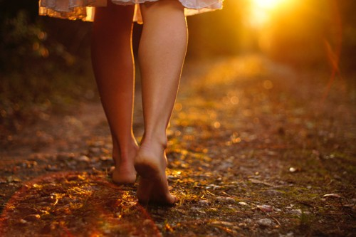 Legs of barefooted woman wearing a knee-length dress walking along a path towards the sunset