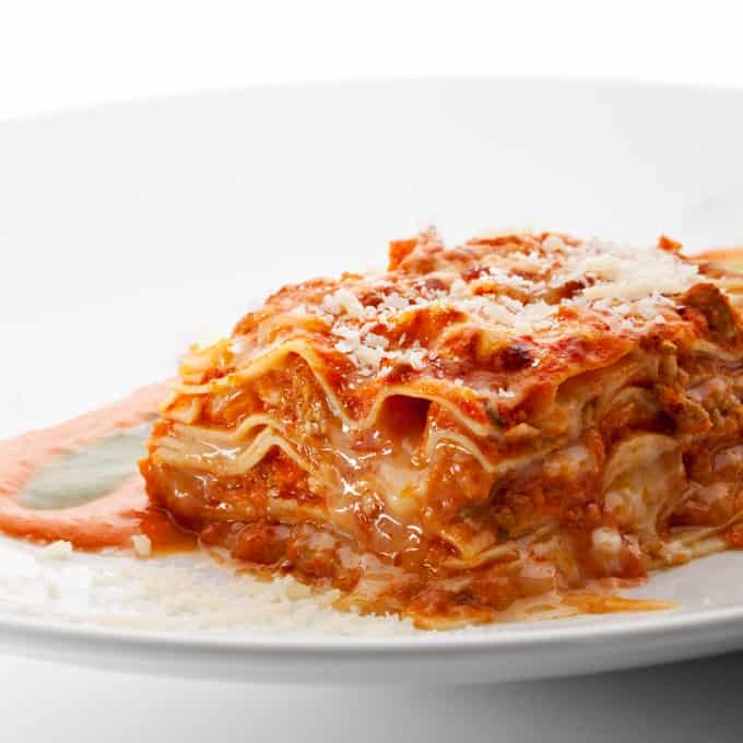 Piece of chicken parmesan lasagna on white dinner plate.