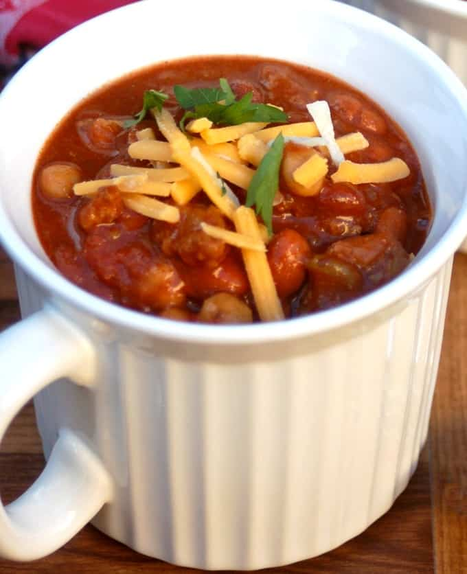 Mug of Three Bean Turkey Sausage Chili garnished with shredded cheese and cilantro