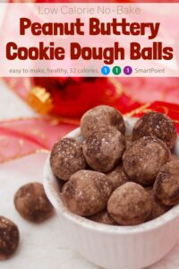 No-Bake Peanut Butter Cookie Dough Balls in white bowl with red holiday ornaments in the background.