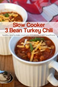 Slow cooker 3-bean turkey sausage chili in white mug topped with shredded cheese.