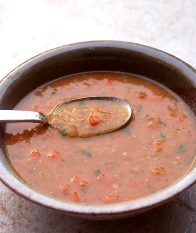 Spicy red lentil soup in a bowl with a spoon