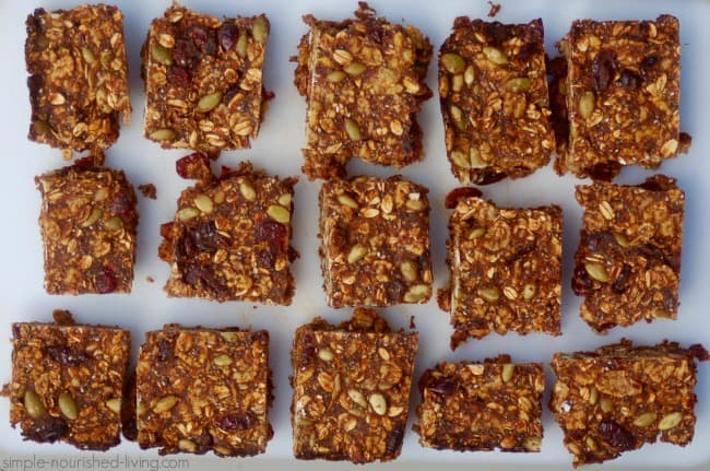 Overhead view of a tray with cut breakfast bars with oats, pumpkin seeds and dried fruit