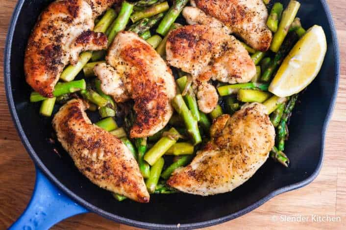 chicken breasts asparagus and lemon wedges in cast iron pan