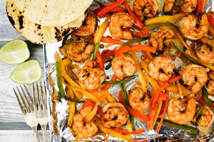 Sheet pan with roasted shrimp fajitas and tortillas