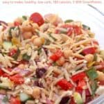 Healthy orzo pasta salad with chickpeas, cucumber, tomatoes, kalamata olives and feta cheese in a glass bowl.