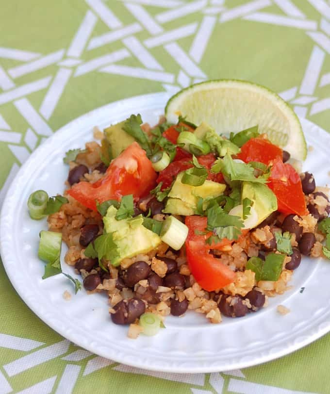 Cauliflower rice and beans topped with avocado chunks and fresh chopped tomatoes and cilantro.