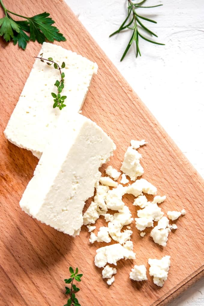 Feta cheese on wood cutting board with fresh rosemary, thyme and parsley herbs.