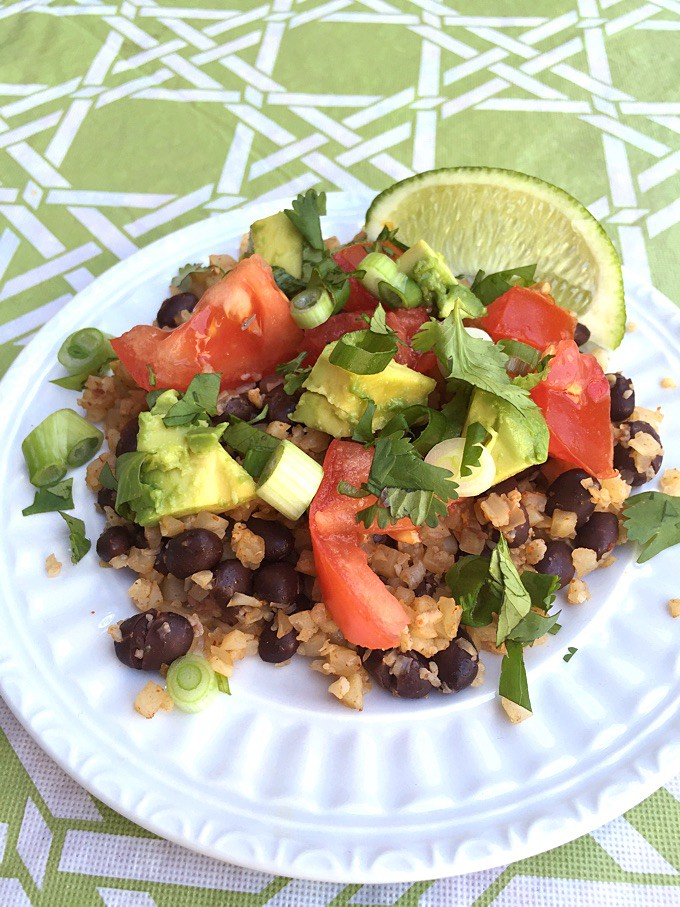 Healthy plate of cauliflower rice with black beans topped with tomatoes, chopped avocado, cilantro and lime wedge