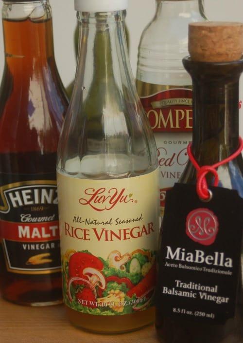 Bottles of malt vinegar, rice vinegar, red wine vinegar and balsamic vinegar.