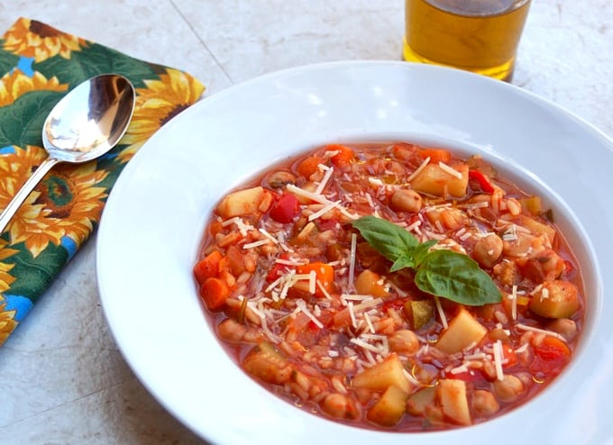 Summer vegetable soup topped with fresh basil and shredded Parmesan cheese in white bowl.