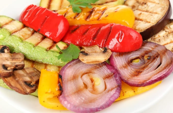 Delicious grilled vegetables (onions, zucchini, eggplant, red and yellow bell peppers and mushrooms) on white plate close-up