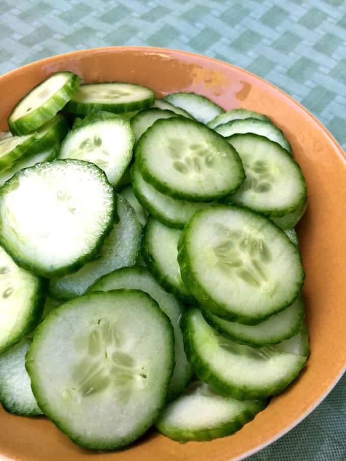 Sliced cucumber salad in brown bowl.