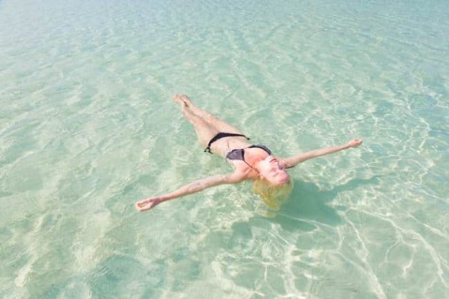 Woman in bikini floating in clear water with arms outstretched.