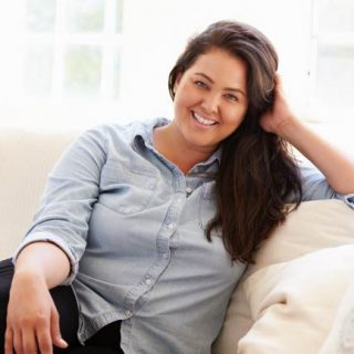 Pretty woman with long dark hair wearing light blue blouse sitting on sofa