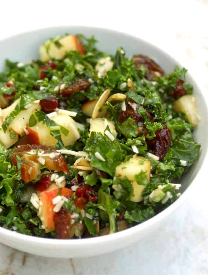 Healthy kale salad with chopped apples and dates in white bowl.