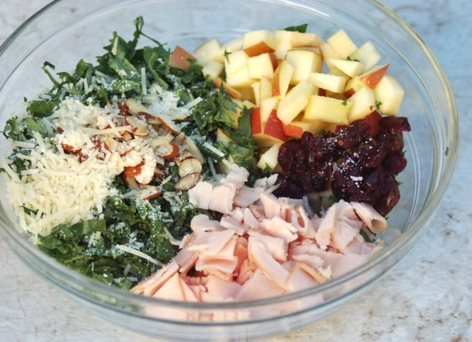 Chopped kale, shredded parmesan cheese, sliced almonds, chopped turkey, chopped apple and sliced dates in glass bowl.
