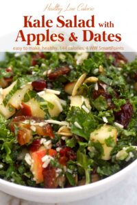 Kale salad with chopped fresh apples and dates in white serving bowl.