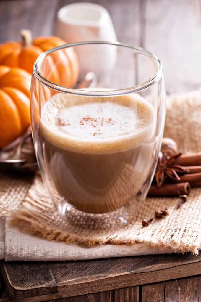 Pumpkin spice latte in glass with spices and baby pumpkins on wooden table.