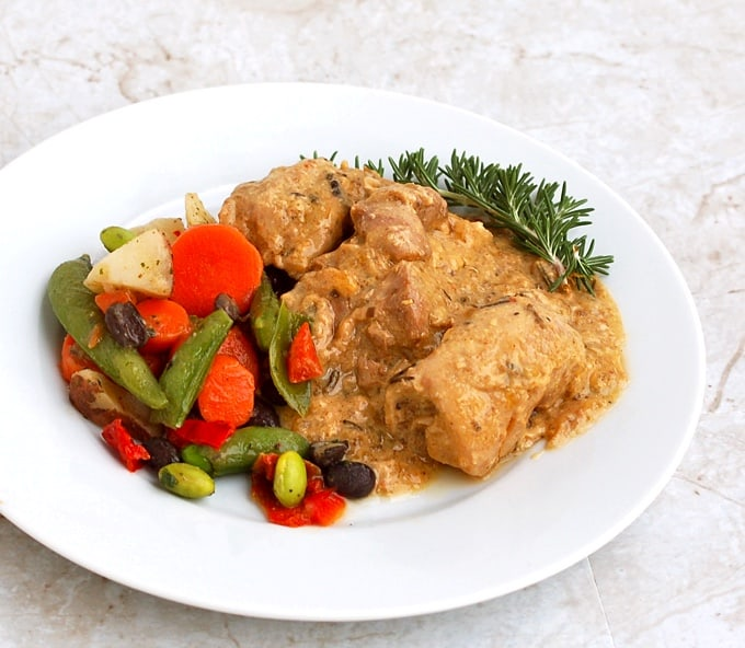 Slow Cooker Mustard Maple Chicken with fresh rosemary and vegetables on white dinner plate.