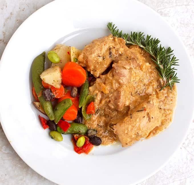 Maple mustard chicken garnished with fresh rosemary on white dinner plate with vegetables.