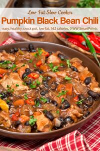 Slow Cooker Pumpkin Black Bean Chili in brown serving dish on table with chili peppers.