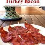 Crispy air fryer turkey bacon on a plate on wooden table.