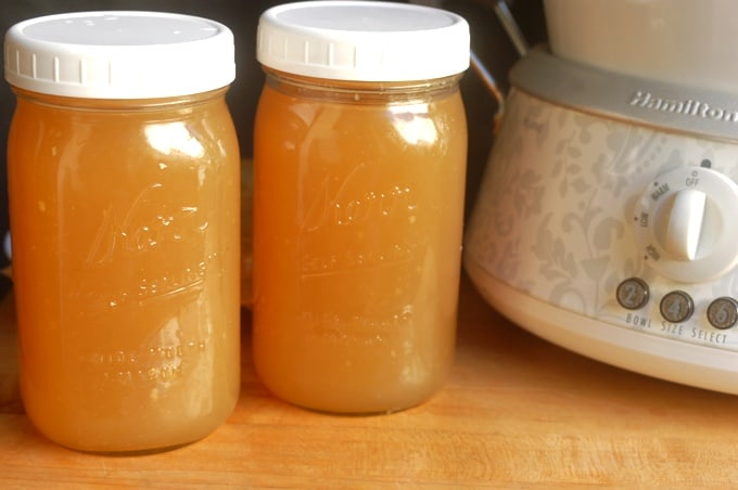 Two mason jars filled with crock pot turkey bone broth sitting near crock pot.