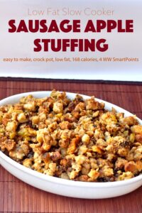 Slow Cooker Sausage Apple Stuffing in white serving dish on wooden mat.