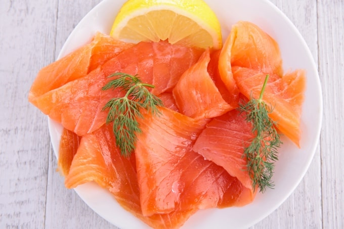 Smoked salmon slices with lemon wedge and fresh dill on a white plate