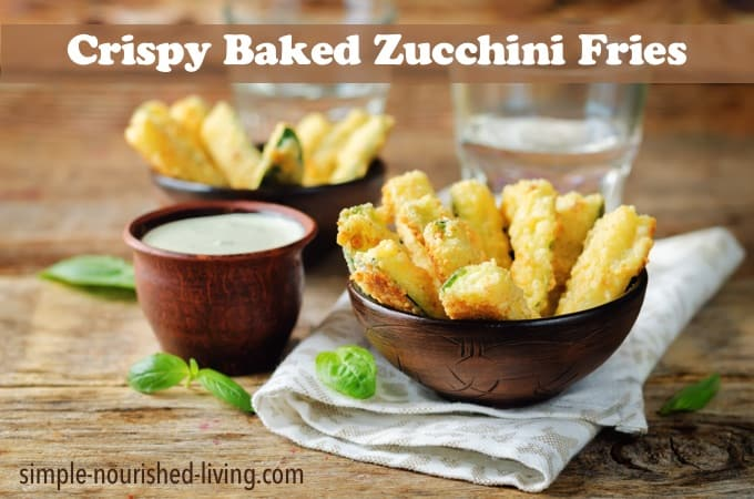Baked Zucchini Fries with Pesto Greek yogurt sauce on a wood background.