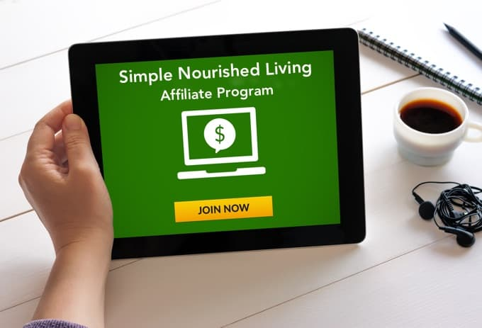 Hand holding tablet with Simple Nourished Living Affiliate Program concept on screen