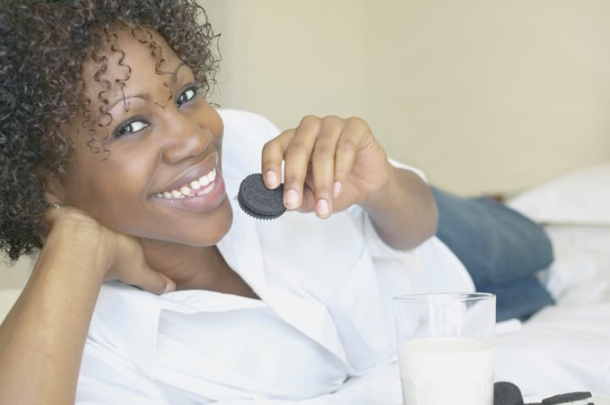 African American Woman Wearing White Blouse Eating a Cookie