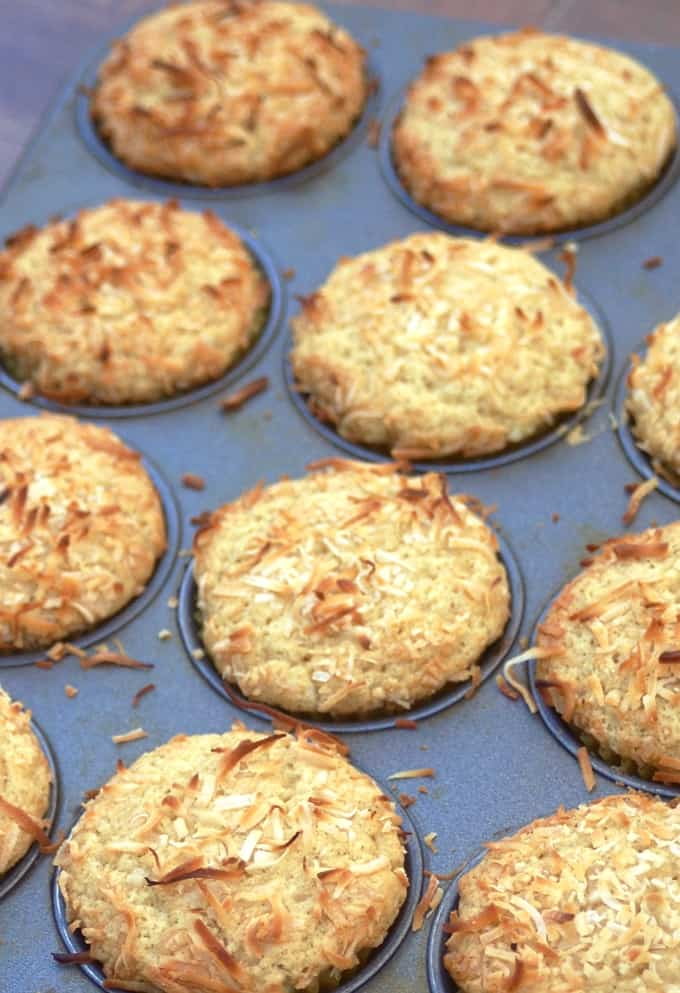 Baked golden brown coconut muffins in muffin pan.