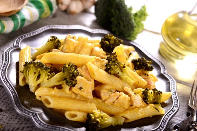 Penne pasta with broccoli and chicken on pewter colored plate