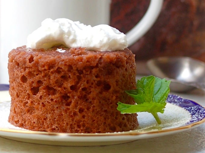 321 Microwave mug cake on a plate with whipped cram and sprig of mint